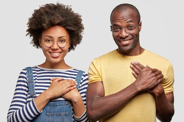 Koncepcja ludzie, pochodzenie etniczne i wdzięczność. uśmiechnięta młoda kobieta i mężczyzna trzymają ręce na klatce piersiowej