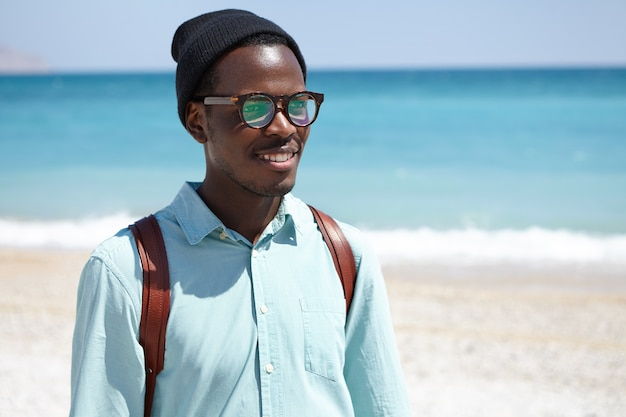 Koncepcja ludzie, podróże, wakacje i turystyka. radosny młody ciemnoskóry mężczyzna z plecakiem cieszący się malowniczym widokiem i morzem podczas letnich wakacji w kurorcie, spacerując samotnie po plaży