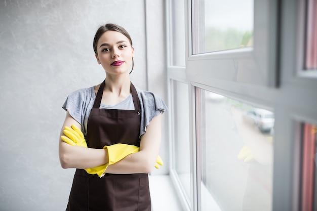 Koncepcja ludzie, prace domowe i sprzątanie - szczęśliwa kobieta sprzątanie stołu w kuchni domowej