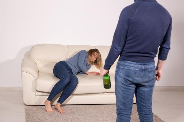Koncepcja ludzie, przemoc i nadużycia - mężczyzna pijący alkohol, podczas gdy żona leży na kanapie