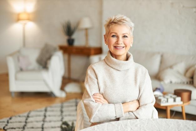 Koncepcja ludzie, przytulność, domowość i sezon. urocza piękna emerytka spędzająca wolny czas w domu z pewnym uśmiechem, trzymając ręce skrzyżowane na piersi