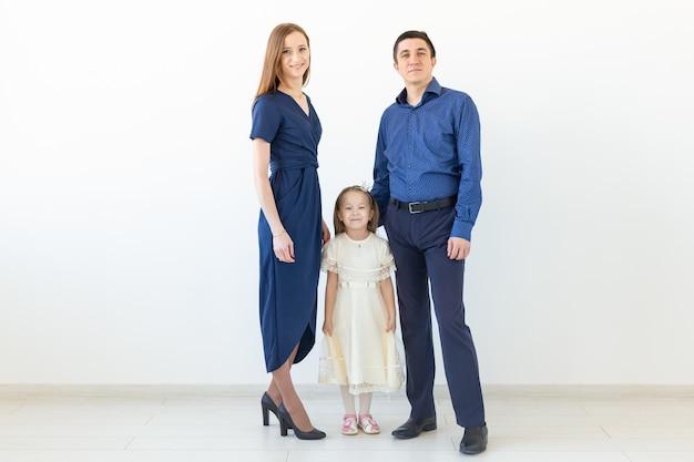 Koncepcja ludzie, rodzina i szczęście - szczęśliwa rodzina z dzieckiem na białej ścianie.