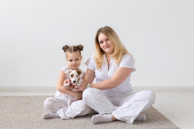 Koncepcja ludzie, rodzina i zwierzęta - matka i córka siedzi na podłodze z szczeniakiem jack russell terrier
