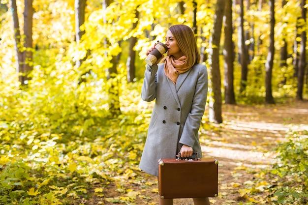 Koncepcja ludzie, sezon i moda - młoda kobieta pije kawę w parku jesień