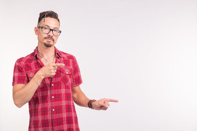 Koncepcja ludzie, styl i moda - młody przystojny mężczyzna w czerwonej koszuli na białej ścianie, wskazując