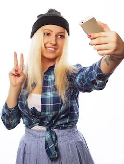 Koncepcja ludzie, styl życia i technologia: ładna nastolatka w kapeluszu, robi selfie swoim smartfonem - na białym tle