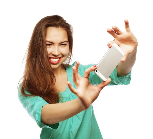 Koncepcja ludzie, styl życia i technologia: ładna nastolatka w zielonej koszuli, robi selfie swoim smartfonem - na białym tle