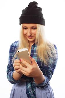 Koncepcja ludzie, styl życia i technologia: ładna nastolatka ze smartfonem - na białym tle