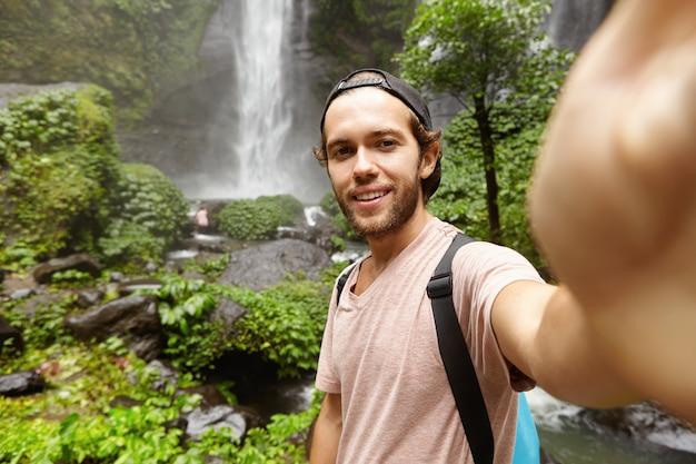 Koncepcja ludzie, styl życia, natura i przygoda. stylowy młody podróżnik z plecakiem robi selfie w lesie deszczowym z wodospadem