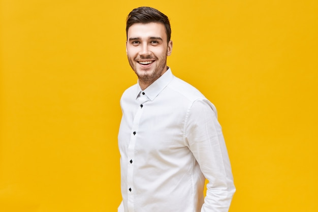 Koncepcja ludzie, styl życia, sukces i zaufanie. wesoły atrakcyjny młody mężczyzna rasy kaukaskiej na sobie formalne stylowe ubrania pozowanie na białym tle z pewną szerokim uśmiechem