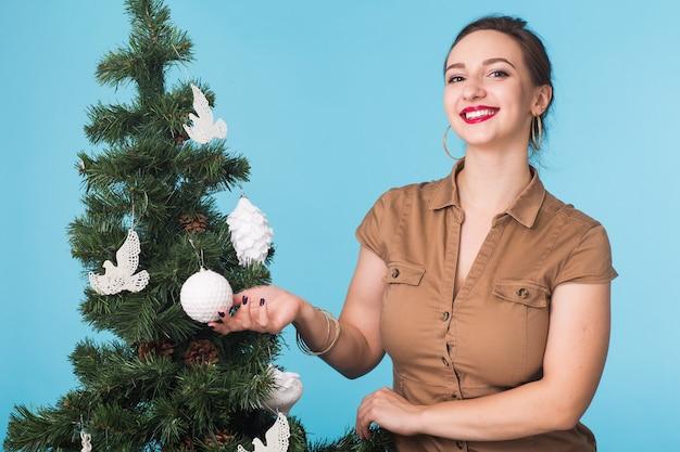 Koncepcja ludzie, święta i boże narodzenie - kobieta dekorująca choinkę na niebieskiej przestrzeni
