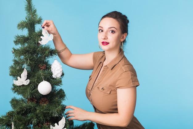 Koncepcja ludzie, święta i boże narodzenie - kobieta dekorująca choinkę na niebieskiej ścianie.