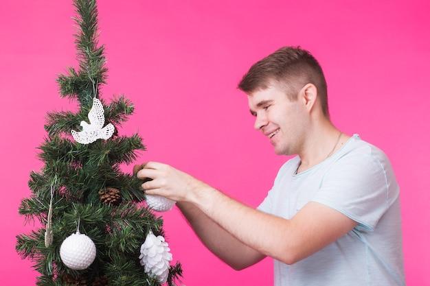 Koncepcja ludzie, święta i boże narodzenie - młody człowiek ozdabia choinkę na różowej ścianie.
