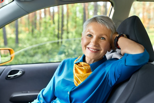 Koncepcja ludzie, transport, podróże i wypoczynek. portret pięknej eleganckiej kobiety w średnim wieku, siedzącej wygodnie na siedzeniu pasażera