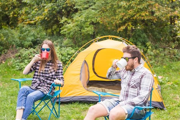 Koncepcja ludzie, turystyka i natura - cute para siedzi w pobliżu żółtego namiotu