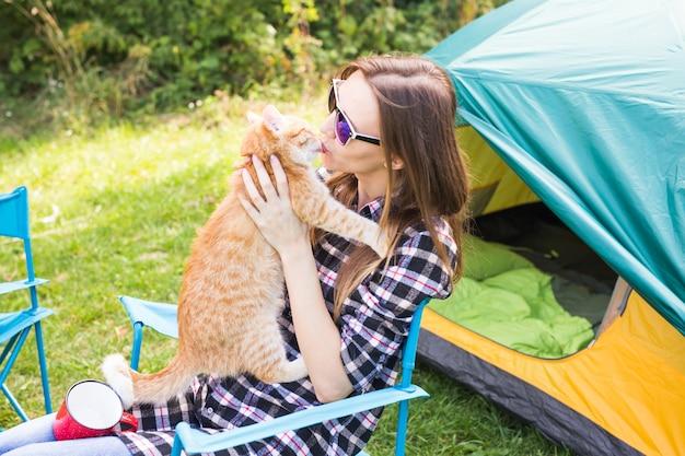 Koncepcja ludzie, turystyka letnia i natura - młoda kobieta z kotem w pobliżu namiotu