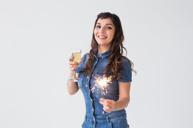 Koncepcja ludzie, uroczystości i wakacje - urocza kobieta z brylantem i kieliszek szampana na białym tle z miejsca kopiowania.