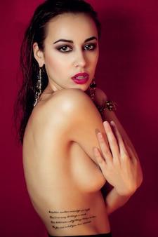 Koncepcja ludzie, uroda, moda, styl życia i kolor - piękna seksowna brunetka dziewczyna pozuje nago w czarnej wysokiej bieliźnie w studio na tle czerwonego lub winnego. przestrzeń reklamowa
