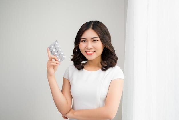 Koncepcja ludzie, uroda, opieka zdrowotna i medycyna - szczęśliwa młoda kobieta trzyma pakiet tabletek w pokoju