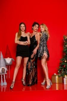 Koncepcja ludzie, wakacje i glamour - przetańczmy całą noc! pełna długość trzech wesołych młodych, elegancko ubranych kobiet świętujących nowy rok, boże narodzenie na czerwonym tle, pozowanie