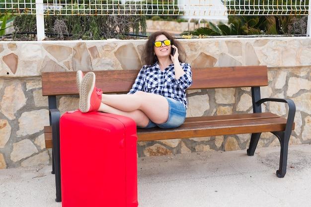 Koncepcja ludzie, wakacje i podróże - młoda kobieta siedzi z nogami na walizce na zewnątrz.