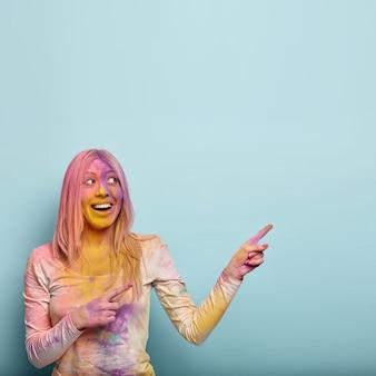 Koncepcja ludzie, wakacje i promocja. jasna, radosna kobieta świętuje święto holi, wskazuje na prawy górny róg, będąc w dobrym nastroju, ma kolorowy proszek na twarzy włosów i wolną przestrzeń powyżej