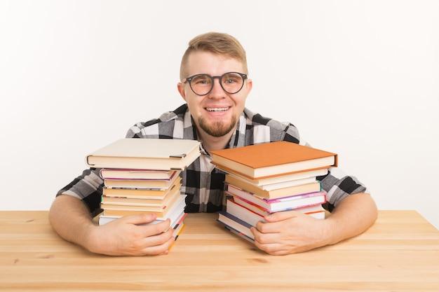 Koncepcja ludzie, wiedza i edukacja - facet siedzi przytulanie książkę przy drewnianym stole