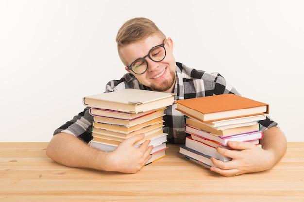 Koncepcja ludzie, wiedza i edukacja - uśmiechnięty mężczyzna siedzi przy drewnianym stole z książkami