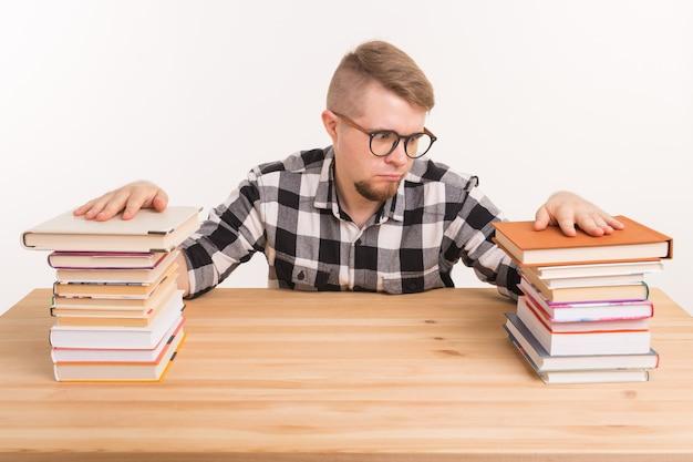 Koncepcja ludzie, wiedza i edukacja - zmęczony student siedzi przy stole z górami książek i nie chce się uczyć.