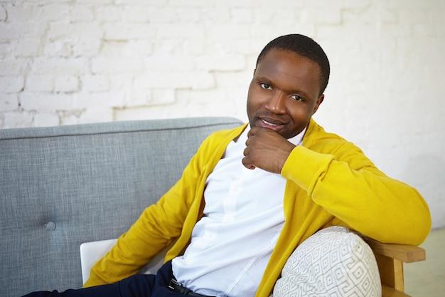 Koncepcja ludzie, wypoczynek, odpoczynek i relaks. kryty strzał przystojny ciemnoskóry mężczyzna w dżinsach, białej koszuli i żółtym swetrze odpoczywa w salonie, siedzi na wygodnej kanapie i uśmiecha się