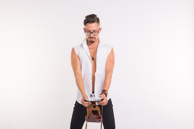 Koncepcja ludzie, zdjęcie i styl - szczęśliwy młody człowiek przy selfie ze starym aparatem fotograficznym na białej powierzchni