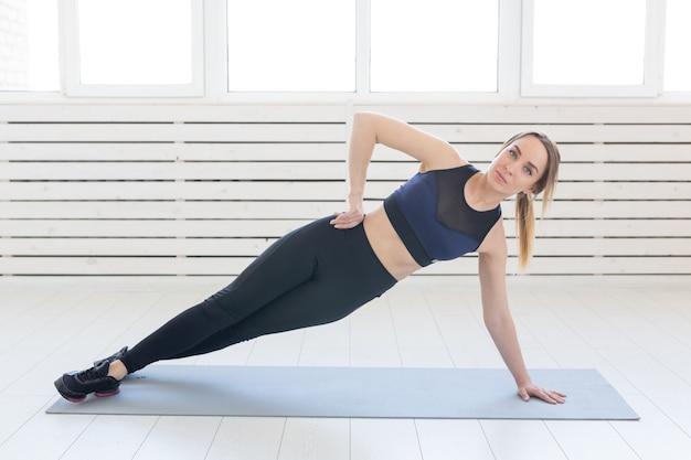 Koncepcja ludzie, zdrowe i fitness - sportowy kobieta robi deski na szarej macie.