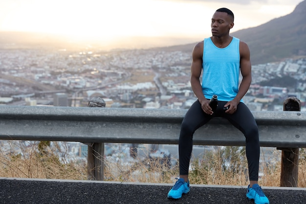Koncepcja ludzie, zdrowie i pochodzenie etniczne. zdjęcie ciemnoskórego mężczyzny w stroju sportowym, niosącego butelkę z wodą, siedzącego przy znaku drogowym, modelki nad naturą z wolną przestrzenią na reklamę