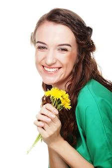 Koncepcja ludzie, zdrowie i spa: piękna młoda kobieta z dużymi żółtymi mleczami