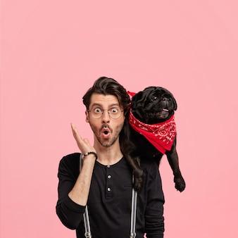 Koncepcja ludzkich emocji. wzruszający, oszołomiony młody hipster ma modną fryzurę, trzyma usta okrągłe, nosi ulubionego czarnego psa, zauważa coś zaskakującego podczas spaceru, stoi przy różowej ścianie