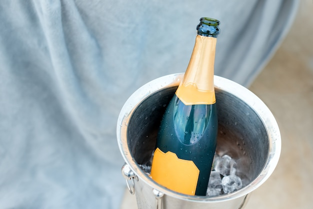 Koncepcja luksusowego życia z butelką szampana w wiaderku z lodem. motyw uroczystości z szampanem martwa.