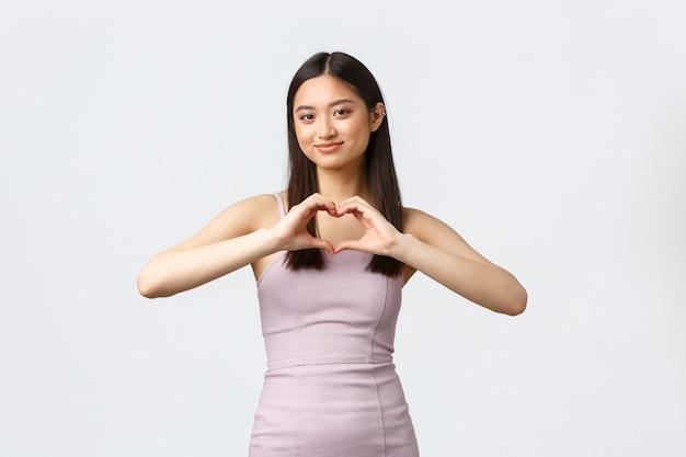 Koncepcja luksusowych kobiet, partii i wakacji. głupia wspaniała azjatka w wieczorowej sukience glamour, pokazująca znak serca i uśmiechnięta, wyrażająca miłość i troskę
