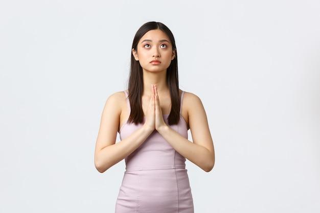 Koncepcja luksusowych kobiet, partii i wakacji. młoda azjatka pełna nadziei w stroju wieczorowym, błagająca, błagająca boga, modląca się i spoglądająca w górę zdeterminowana