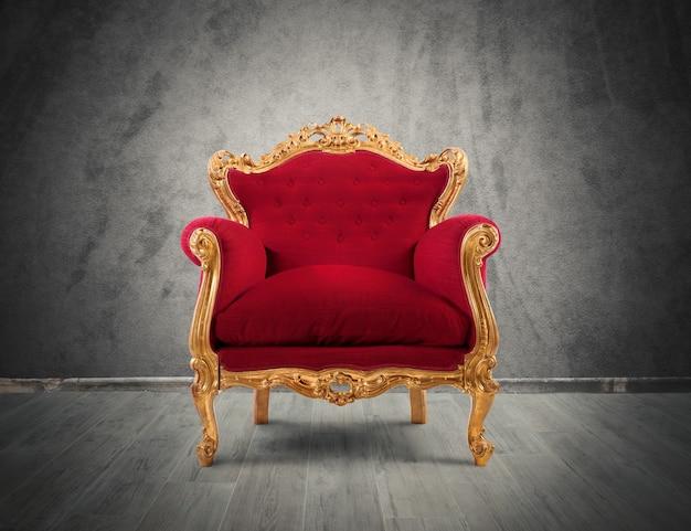Koncepcja luksusu i sukcesu z fotelem z czerwonego aksamitu i złota