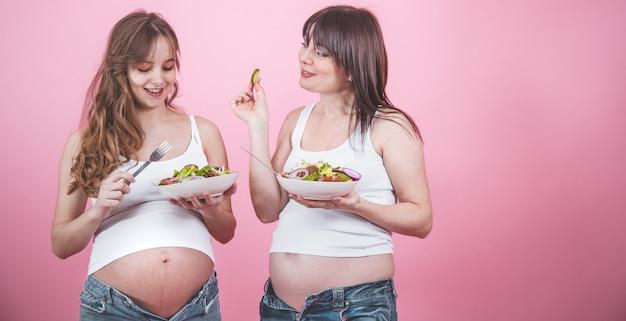 Koncepcja macierzyństwa, dwie kobiety w ciąży jedzenie świeżej sałatki
