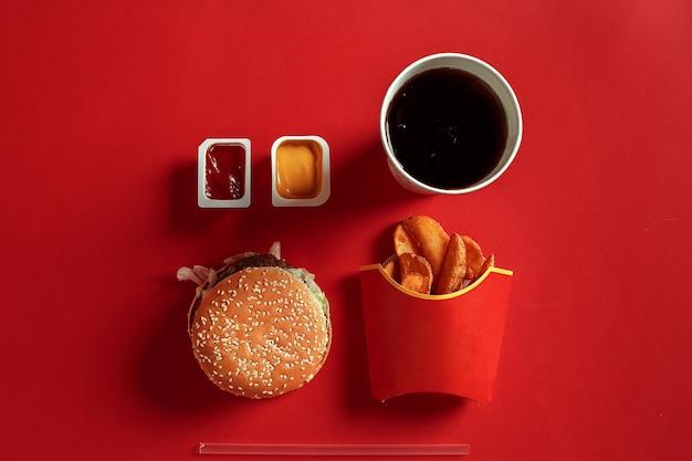 Koncepcja makiety sosu z ziemniakami burger i napoju na czerwonym tle miejsca na tekst i logo