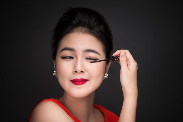 Koncepcja makijażu i kosmetyków. azjatyckie kobiety robi jej makijaż rzęs czarny tusz do rzęs.