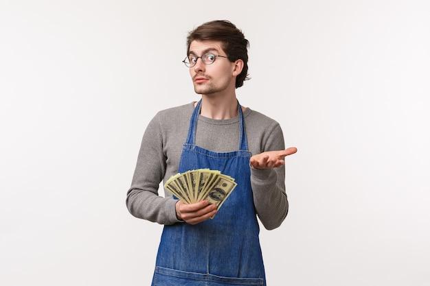 Koncepcja małych firm, finansów i kariery. portret chciwego kaukaskiego mężczyzny w fartuchu, wskazującego ręką na aparat i trzymającego gotówkę, działającego nieświadomego nic nie wiem, nie mów, jak się wzbogacił