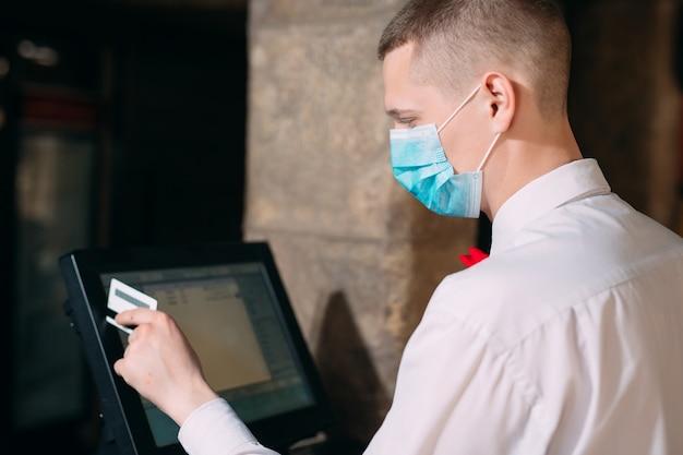 Koncepcja małych firm, ludzi i usług. mężczyzna lub kelner w masce medycznej przy kasie z kasą pracujący w barze lub kawiarni.