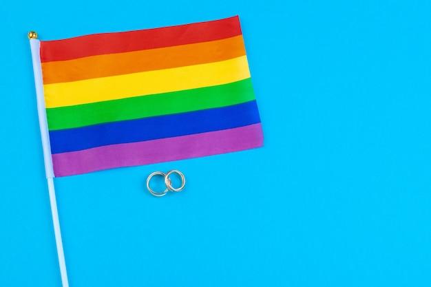 Koncepcja małżeństwa gejowskiego z flagą rainbow i pierścieniami
