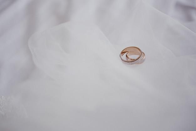 Koncepcja małżeństwa. złote obrączki ślubne na białym welonie. zbliżenie. miejsce na tekst. widok z góry.