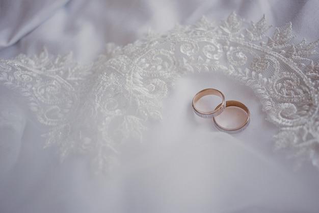 Koncepcja małżeństwa. złote obrączki ślubne na białym welonie