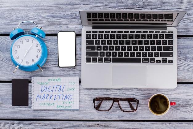 Koncepcja marketingu cyfrowego leżała płasko. laptop z budzikiem i filiżanką kawy.