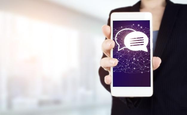 Koncepcja marketingu e-mail i sms. ręka trzymać biały smartphone z cyfrowym hologramem znak e-mail i sms na jasnym tle niewyraźne. koncepcja biznesowa e-mail.
