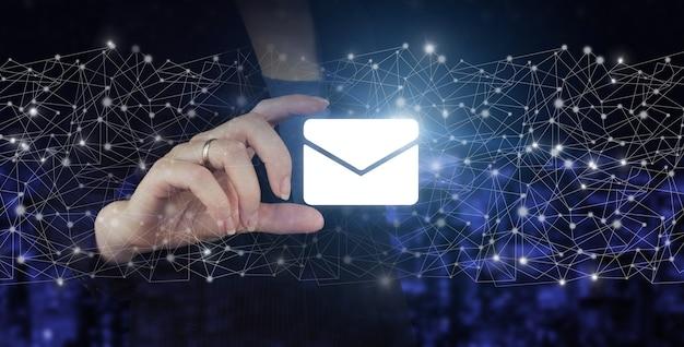 Koncepcja marketingu e-mail i sms. ręka trzymać cyfrowy hologram znak e-mail i sms na ciemnym tle niewyraźne miasta. skontaktuj się z nami koncepcja.